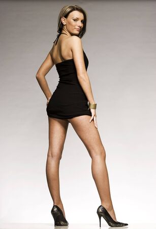 beautiful blonde girl wearing black mini dress and high heeled shoes posing on grey background