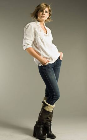beautiful blonde model wearing white shirt, jeans and boots on grey background