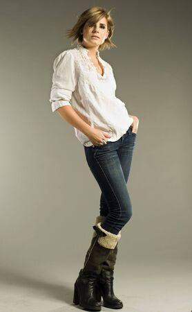 skinny jeans: bella rubia modelo llevaba camisa blanca, jeans y botas sobre fondo gris  Foto de archivo