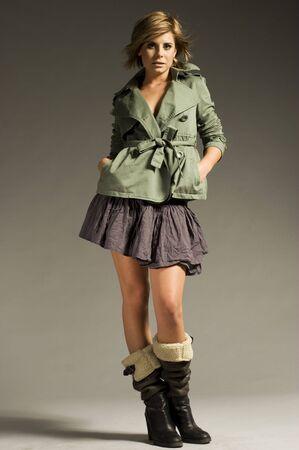 beautiful blonde girl wearing green coat and mini skirt on grey background photo