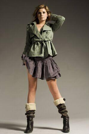 20 25: beautiful blonde girl wearing green coat and mini skirt on grey background Stock Photo