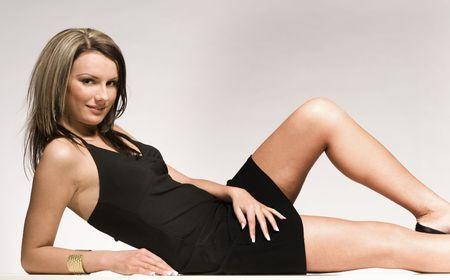 beautriful blond model lying on grey background wearing black mini dress photo