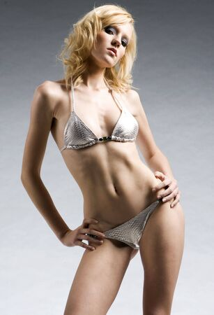 beautiful and sexy blonde model wearing silver bikini posing on grey background