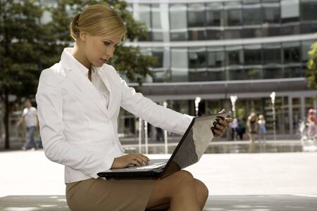 young and attractive blonde businesswoman working on laptop outdoors Stock Photo - 3341489