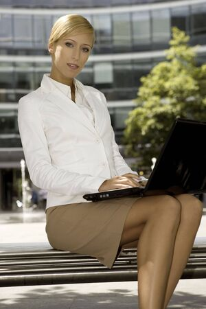 young and attractive businesswoman working on laptop outdoors Stock Photo - 3341488