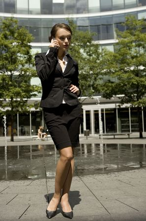 carreer: young and attractive businesswoman talking on the mobile outside Stock Photo