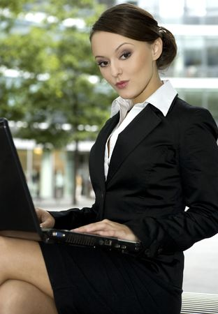 carreer: young and attractive businesswoman working on laptop outdoors