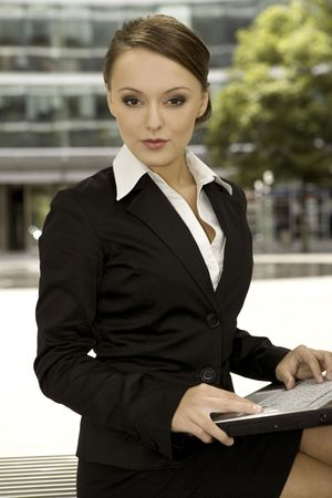 young and attractive brunette businesswoman working on laptop outdoors photo
