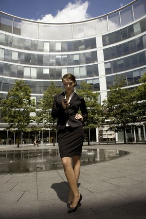 young brunette businesswoman outdoors talking on the phone photo