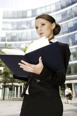 carreer: young brunette businesswoman outdoors with a notebook