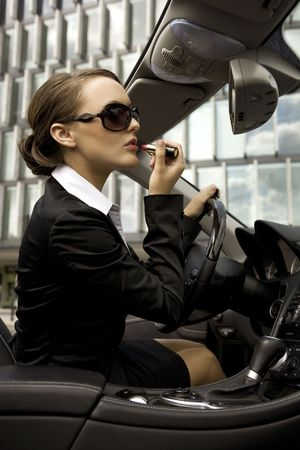 attractive and young businesswoman putting on lipstick in a cabrio car