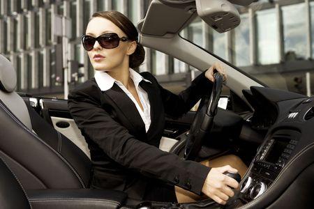 beautiful brunette businesswoman driving a cabrio car photo