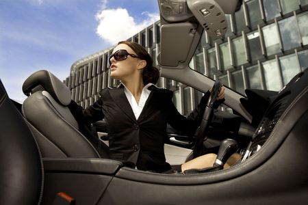 beautiful brunette businesswoman driving a cabrio car photo