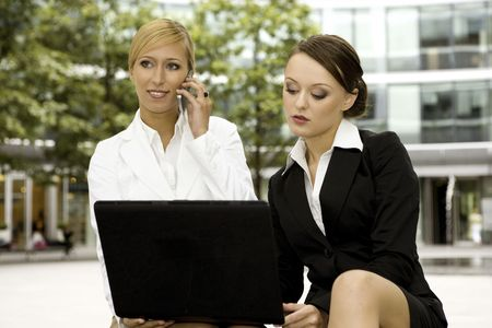 two attractive businesswomen working on laptop outdoors photo