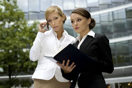 two attractive businesswomen talking on the phone and holding a notebook outdoors photo