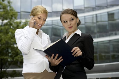 carreer: two attractive businesswomen talking on the phone and holding a notebook outdoors