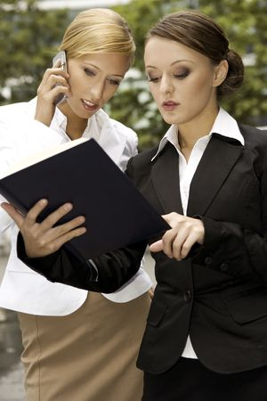 two young businesswomen outdoors talking about business photo