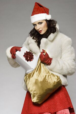 women subtle: beautiful brunette girl wearing Santa costume holding Christmas present on grey background