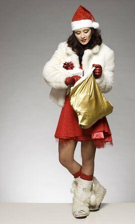 sackful: beautiful brunette girl wearing Santa costume holding Christmas present on grey background