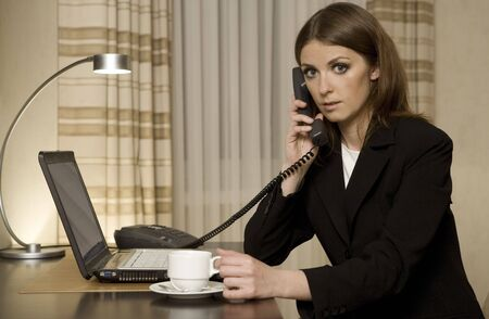young businesswoman talking on the phone and working on a laptop in a hotel room Stock Photo - 3790285