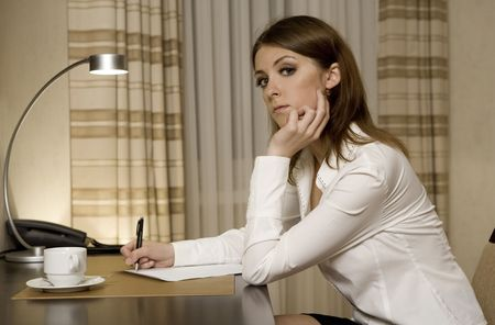 secretary skirt: beautiful young businesswoman sitting at the desk and writing