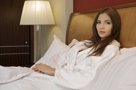 Beautiful brunette woman on a bed Stock Photo - 8814584