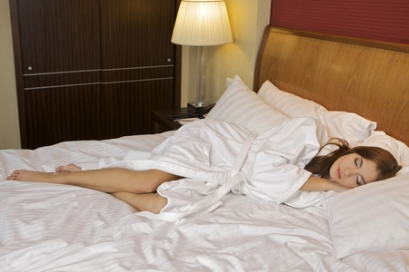lying on back: Above view of young beautiful woman sleeping in bed covered with white silky sheet Stock Photo