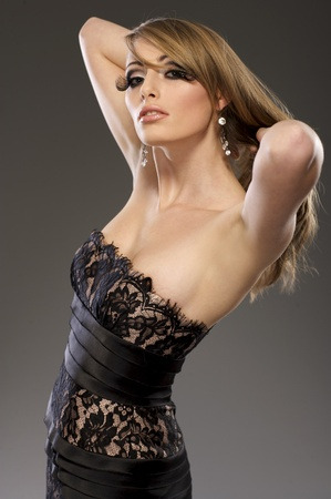 beautiful blond model in black dress posing on grey background photo