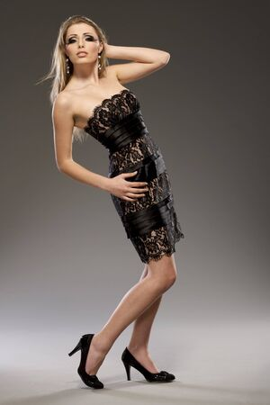 beautiful blond model in black dress posing on grey background photo