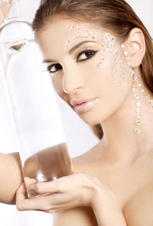picture of lovely woman in diamond make up with big bottle photo