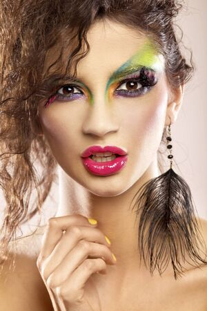 Beautiful young attracive female face with bright fashion multicolored make-up and beauty yellow manicure of fingernails photo