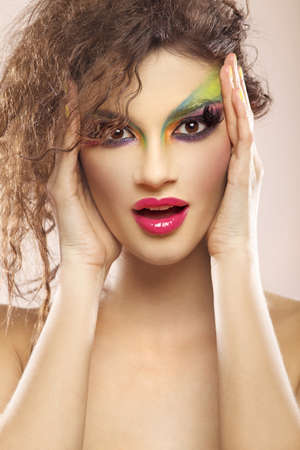 Beautiful young attracive female face with bright fashion multicolored make-up and beauty yellow manicure of fingernails Stock Photo - 9695184
