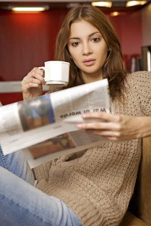 morning routine: mid adult beautiful woman drinking coffee and reading news