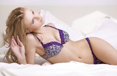 Young sexy blond woman in sexy lingerie on the bed