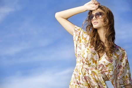 portrait of beautiful and sensuality brunette girl in sunglasses on background blue sky. copy space photo