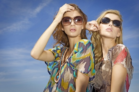 portrait of two beautiful blonde and brunette girl in sunglasses on background blue sky photo