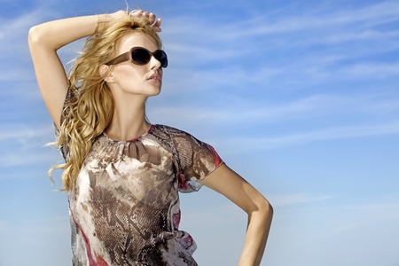 portrait of beautiful blonde girl in sunglasses on background blue sky Stock Photo - 9696005