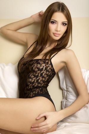 attractive brunette in beautiful black linen in bed