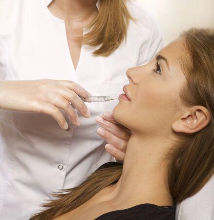latex woman: young beautiful woman having an injection