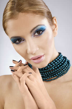 Beautiful young female face with bright fashion multicolored make-up and beauty black manicure of fingernails photo