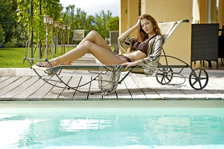 Sexy and beautiful young brunette woman relaxing on deck chair Stock Photo - 9773171