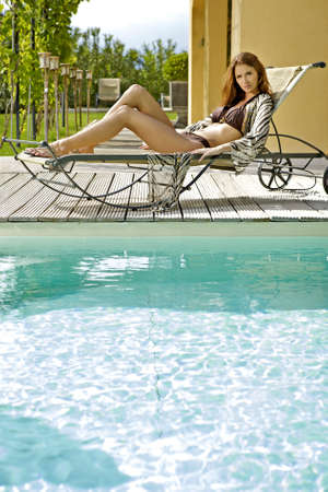 Sexy and beautiful young brunette woman relaxing on deck chair by the pool Stock Photo - 9773158