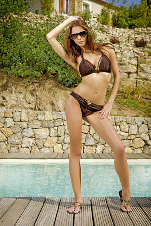 beautiful and sensual attractive brunette in a bikini in the garden by the pool photo
