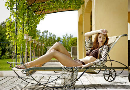Sexy and beautiful young brunette woman relaxing on deck chair photo