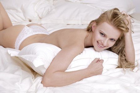 Young sexy blond woman in sexy lingerie on the bed Stock Photo - 9908750