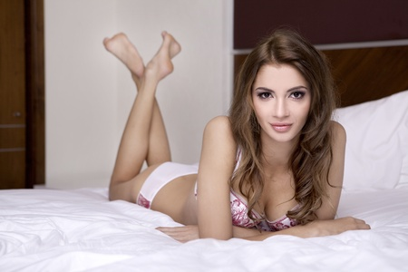 Beautiful young brunette woman in lingerie on the bed Stock Photo - 9936121
