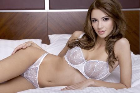 erotico: Joven y bella mujer morena en ropa interior en la cama Foto de archivo