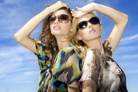 two beautiful blonde girl in sunglasses on background blue sky photo