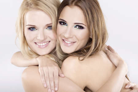 Two smiling attractive girl friends - blond and brunette on white background photo