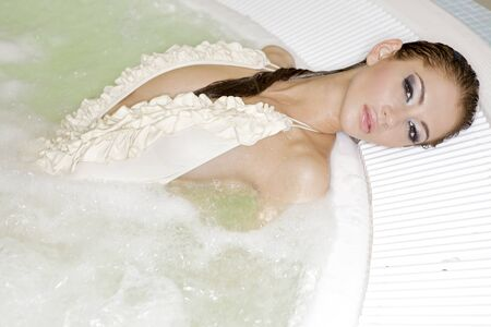 Young beautiful brunette woman in jacuzzi photo